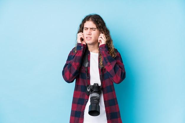 Il giovane uomo caucasico del fotografo ha isolato le orecchie della copertura con le mani.