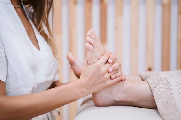 Giovane donna caucasica del fisioterapista che dà un massaggio dei piedi al paziente femminile in clinica. fisioterapia e concetto di cura del corpo