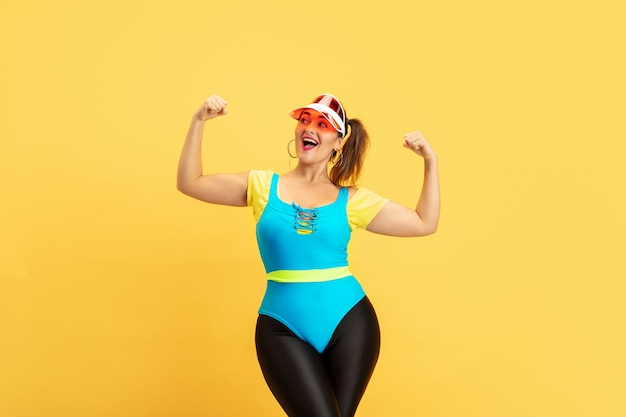 Giovane indoeuropeo plus size modello femminile di formazione sulla parete gialla. copyspace. concetto di sport, stile di vita sano, corpo positivo, moda, stile. donna alla moda che posa sicura, potere della ragazza.