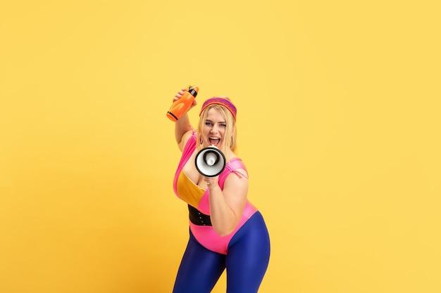 Giovane indoeuropeo plus size modello femminile di formazione sulla parete gialla. copyspace. concetto di sport, stile di vita sano, corpo positivo, moda, stile. donna alla moda con bottiglia e boccaglio.