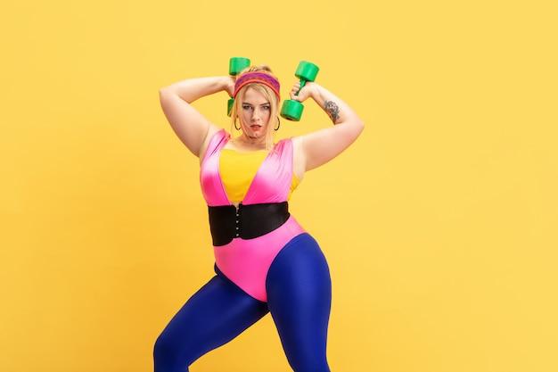 Giovane modello femminile caucasico plus size che si allena su giallo