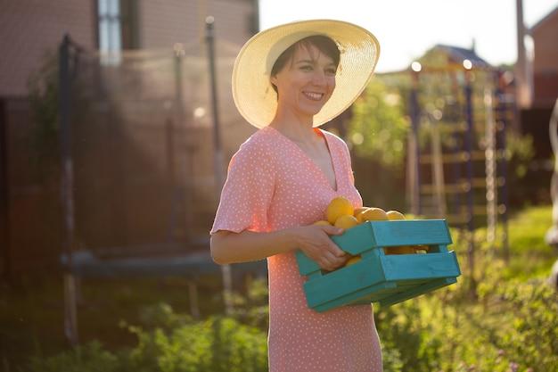 Il giovane giardiniere caucasico della donna positiva in cappello e vestito dentellare tiene la scatola con i limoni nelle sue mani il giorno di estate pieno di sole. concetto di agricoltura e giardinaggio biologico