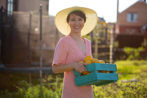 Il giovane giardiniere caucasico della donna positiva in cappello e vestito dentellare tiene la scatola con i limoni nelle sue mani su