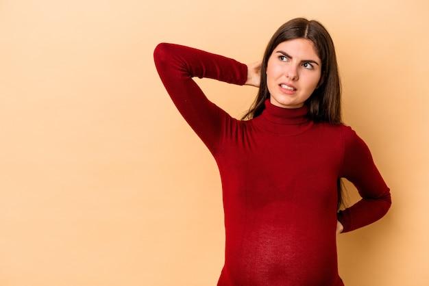 Giovane donna incinta caucasica isolata su fondo beige che tocca la parte posteriore della testa, pensa e fa una scelta.