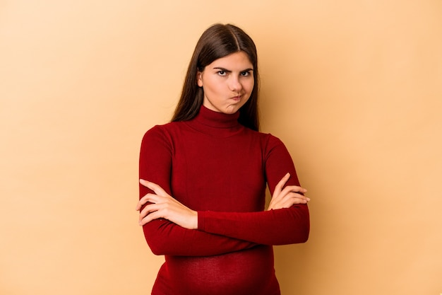Giovane donna incinta caucasica isolata sulla parete beige insoddisfatta dell'espressione sarcastica.