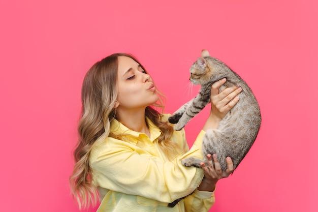 Una giovane donna bionda carina caucasica con una camicia gialla tiene in mano un gatto ammirandolo isolato su un muro rosa di colore brillante