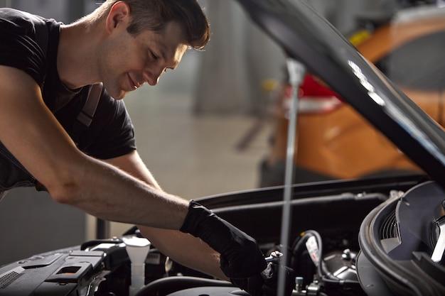 Giovane meccanico professionista caucasico in un servizio di auto