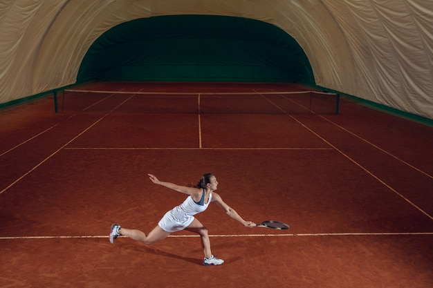 Giovane indoeuropea sportiva professionista giocando a tennis sulla parete del campo sportivo