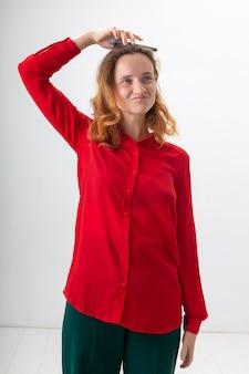 La giovane donna caucasica dai capelli rossi con i capelli lunghi in camicia rossa isolata su sfondo bianco tiene lo smartphone in mano, lo mette in testa. donna che scherza con il cellulare