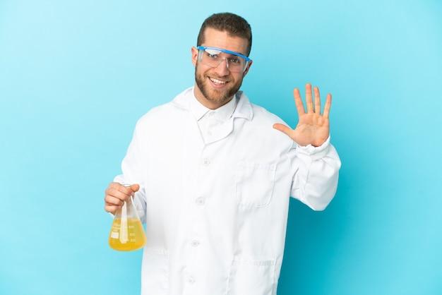 Giovane uomo scientifico caucasico isolato sull'azzurro che conta cinque con le dita