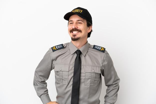 Giovane uomo caucasico di sicurezza isolato su sfondo bianco in posa con le braccia all'anca e sorridente