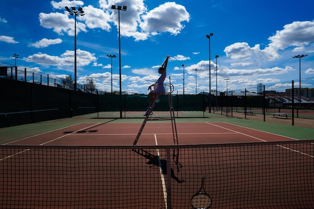 Giovane tennista femminile sexy caucasico sul campo vicino alla scala dell'arbitro.