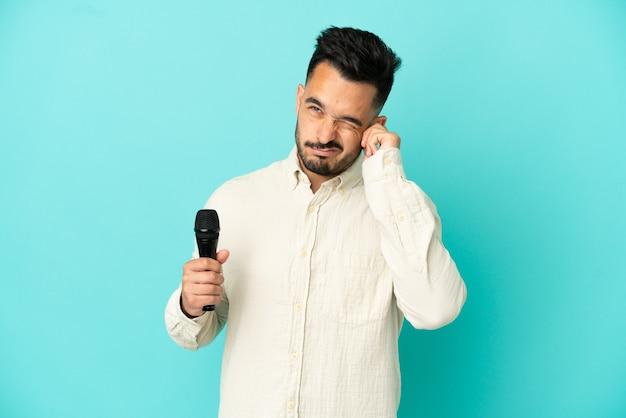 Giovane cantante caucasico uomo isolato su sfondo blu frustrato e che copre le orecchie