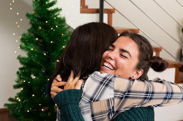 Le giovani sorelle caucasiche si abbracciano il giorno di natale felicità affetto amore vacanza