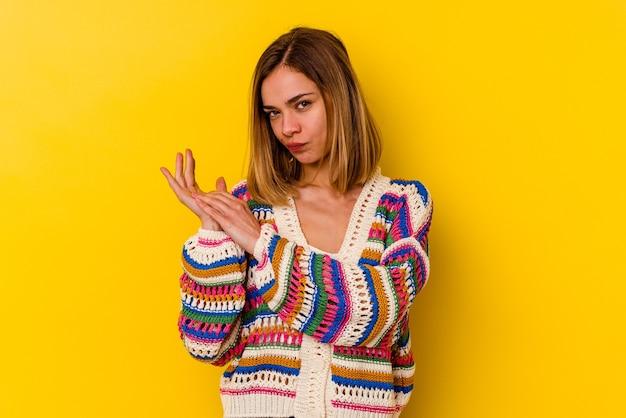 Giovane donna magra caucasica isolata su giallo sentendosi energica e confortevole, strofinando le mani fiducioso.