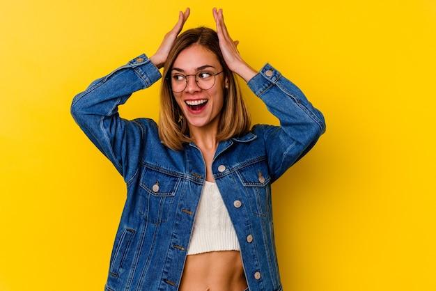 Giovane donna magra caucasica isolata su giallo urlando, molto eccitata, appassionata, soddisfatta di qualcosa.