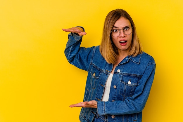 Giovane donna magra caucasica isolata su giallo scioccata e stupita tenendo uno spazio di copia tra le mani.