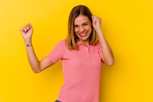 Giovane donna magra caucasica isolata sulla parete gialla ballando e divertendosi.
