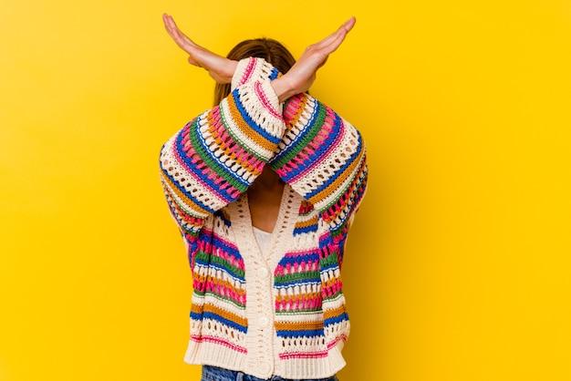 Giovane donna magra caucasica isolata sulla parete gialla mantenendo due braccia incrociate