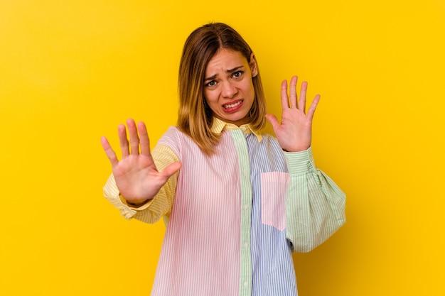 Giovane donna magra caucasica isolata sulla parete gialla che rifiuta qualcuno che mostra un gesto di disgusto