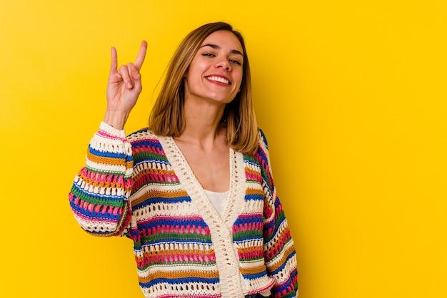 Giovane donna magra caucasica isolata sulla parete gialla che mostra un gesto di corna