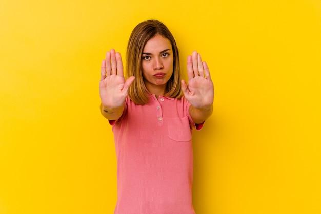 Giovane donna magra caucasica isolata sul muro giallo in piedi con la mano tesa che mostra il segnale di stop, impedendoti