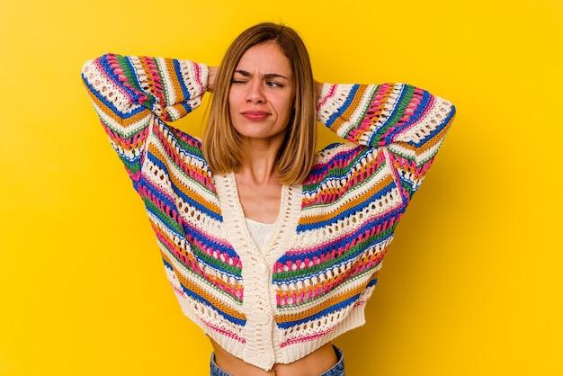 Giovane donna magra caucasica isolata sul muro giallo che soffre di dolore al collo a causa dello stile di vita sedentario.
