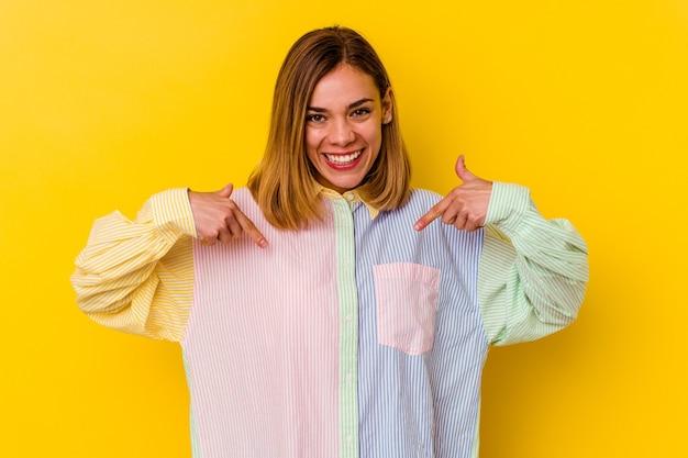 Giovane donna magra caucasica isolata sul muro giallo sorpreso indicando con il dito, sorridendo ampiamente. Foto Premium