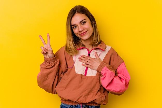 Giovane donna magra caucasica isolata sulla parete gialla che presta giuramento, mettendo la mano sul petto.