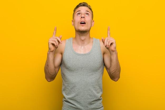 Giovane uomo caucasico di sport che indica a testa in giù con la bocca aperta.