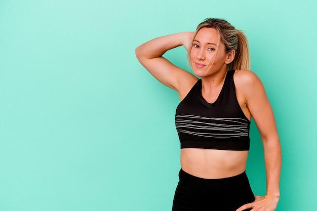 Giovane donna caucasica di sport isolata sulla parete blu che tocca la parte posteriore della testa, pensando e facendo una scelta.