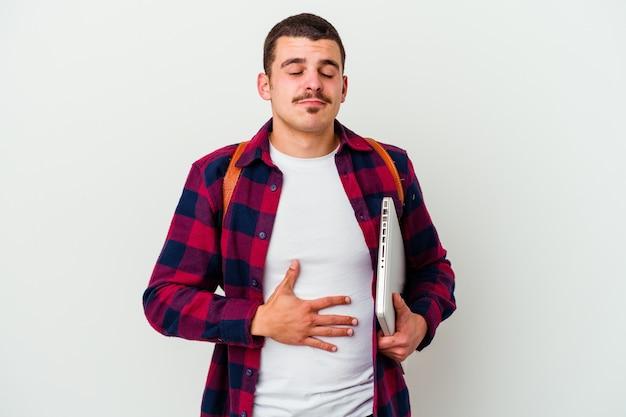 Il giovane uomo caucasico dell'allievo che tiene un computer portatile isolato su priorità bassa bianca tocca la pancia, sorride delicatamente, mangiando e concetto di soddisfazione.