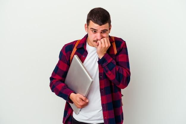 Uomo giovane studente caucasico che tiene un computer portatile isolato sulle unghie mordaci della parete bianca, nervoso e molto ansioso.