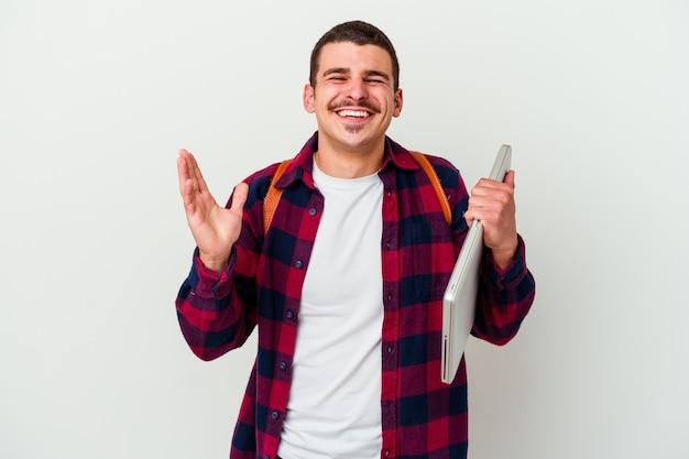 Uomo giovane studente caucasico che tiene un computer portatile isolato sulla parete bianca gioiosa che ride molto. concetto di felicità.