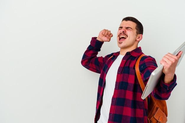 Uomo giovane studente caucasico che tiene un computer portatile isolato sul muro bianco alzando il pugno dopo una vittoria, concetto di vincitore.