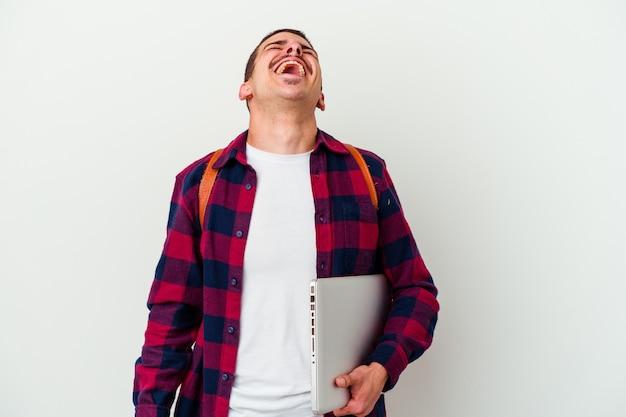 Il giovane uomo caucasico dell'allievo che tiene un computer portatile isolato sulla parete bianca si è rilassato e risata felice, collo allungato mostrando i denti.