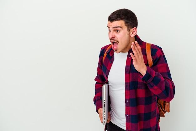 L'uomo giovane studente caucasico che tiene un computer portatile su bianco grida forte, tiene gli occhi aperti e le mani tese.