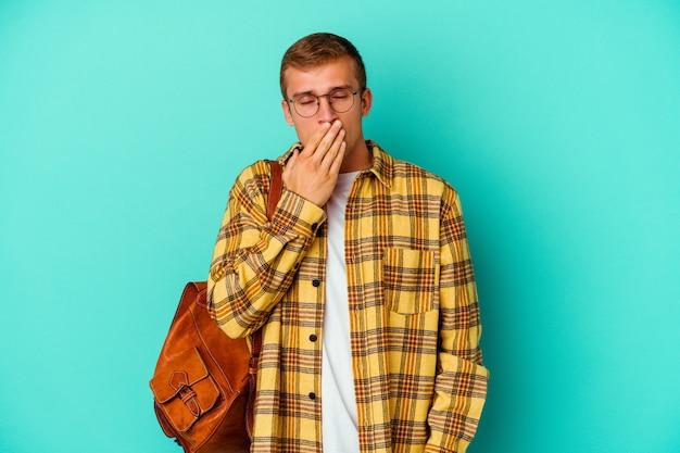 Giovane studente caucasico isolato su sfondo blu che sbadiglia mostrando un gesto stanco che copre la bocca con la mano.