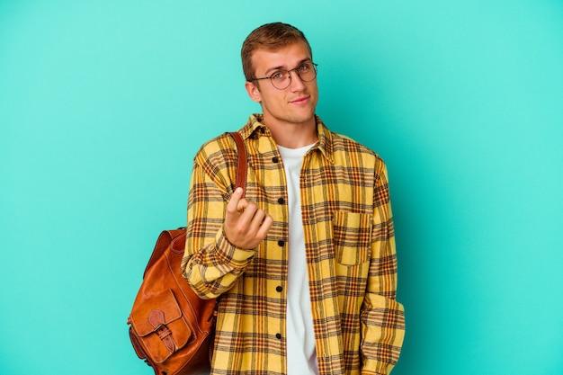 Uomo giovane studente caucasico isolato su blu che punta con il dito contro di te come se invitando si avvicinano