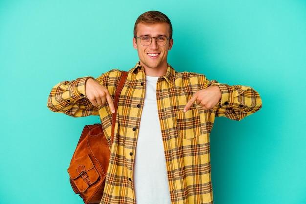 Uomo giovane studente caucasico isolato su punti blu verso il basso con le dita, sensazione positiva.