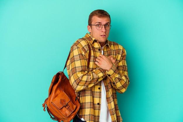 Uomo giovane studente caucasico isolato su blu spaventato e impaurito.