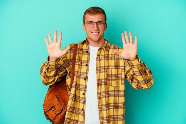 Uomo giovane studente caucasico isolato sul blu che mostra il numero dieci con le mani.