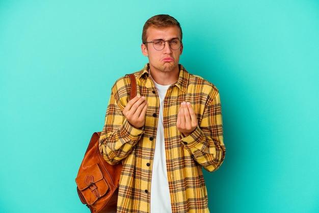 Uomo giovane studente caucasico isolato sull'azzurro che mostra che non ha soldi.