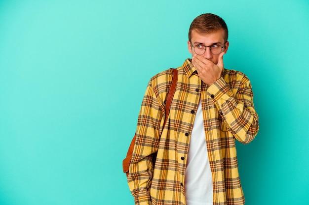Uomo giovane studente caucasico isolato su blu premuroso guardando uno spazio di copia che copre la bocca con la mano.