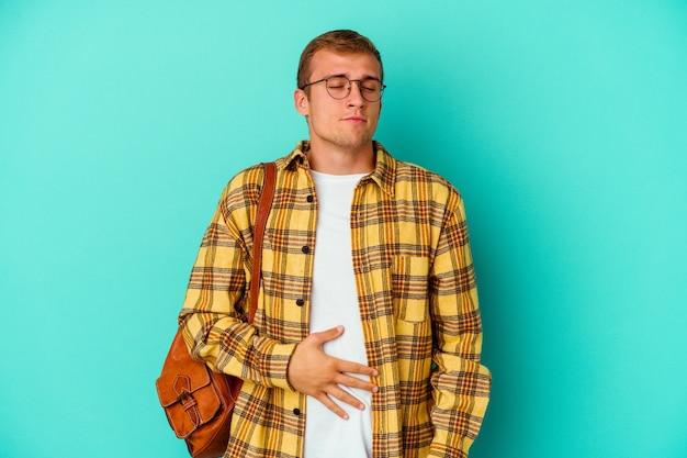 Uomo giovane studente caucasico isolato su blu tocca pancia, sorride delicatamente, mangiare e concetto di soddisfazione.