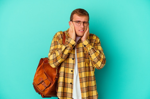 Uomo giovane studente caucasico isolato sul muro blu che copre le orecchie con le mani.