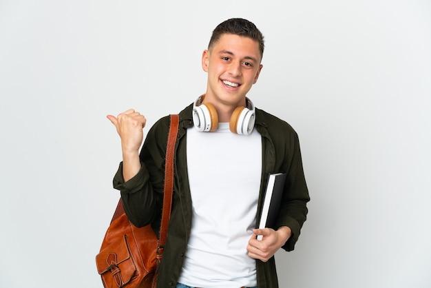 Uomo giovane studente caucasico isolato su sfondo bianco che punta di lato per presentare un prodotto