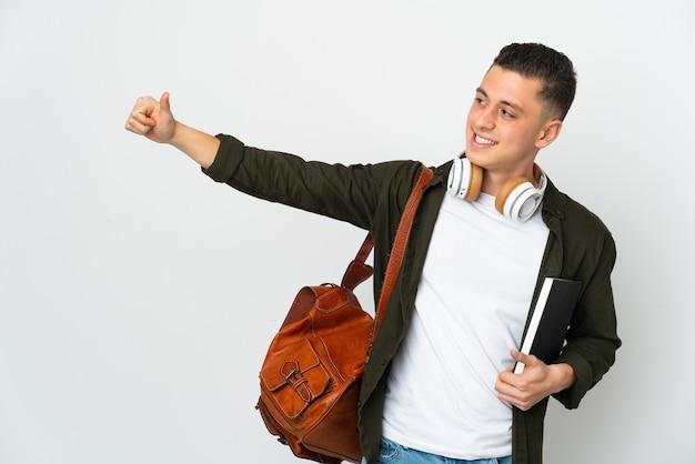 Uomo giovane studente caucasico isolato sulla parete bianca che dà un pollice in alto gesto