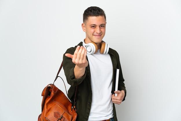 Uomo giovane studente caucasico isolato sul muro bianco che invita a venire con la mano. felice che tu sia venuto