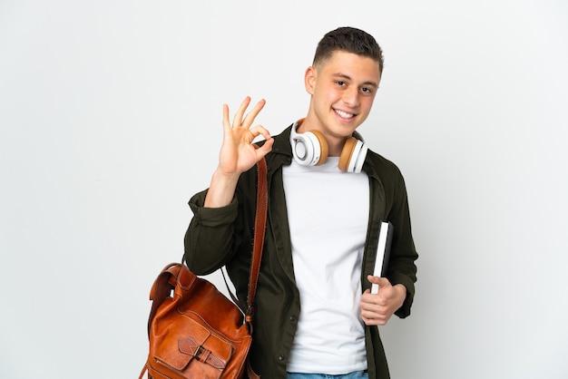 Uomo giovane studente caucasico isolato sulla parete bianca che mostra segno giusto con le dita